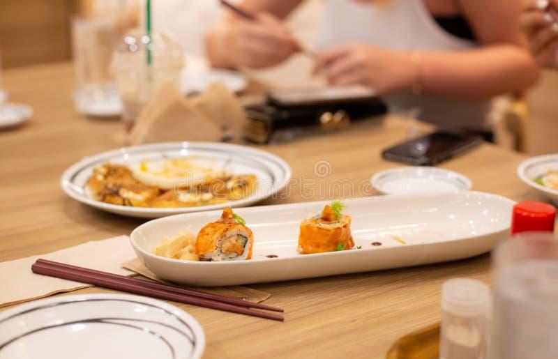Sushilachse rollen mit knusperiger Tempuragarnele, japanischer traditioneller Teller Familienabendessenkonzept lizenzfreies stockfoto