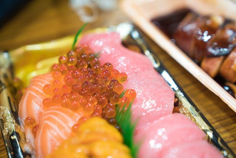 Sushilachse und -andere Sushi werden in der Schaumanlage auf dem tischfertigen vereinbart, um am Kuromon-Fischmarkt, Osaka, Japan lizenzfreie stockbilder
