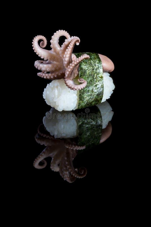 Sushinigiri med bläckfisken på svart bakgrund med reflexion J fotografering för bildbyråer