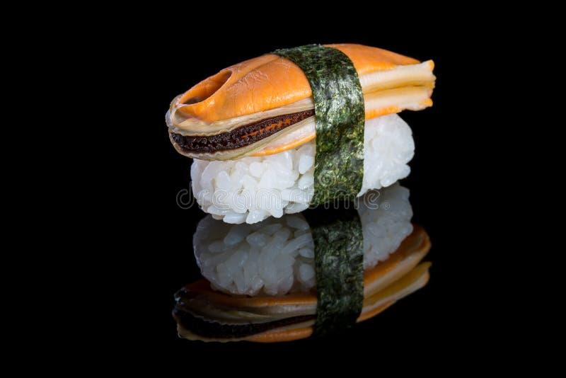 Sushinigiri med musslan på svart bakgrund med reflexion Ja arkivbilder
