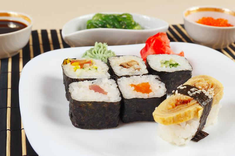 Sushireeks, hiyashi wakame salade, sojasaus en zalmkaviaar op zwarte dichte omhooggaand van de bamboemat stock foto
