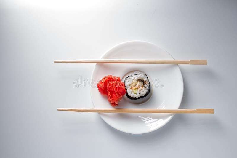 Sushirolle auf Plättchen mit Essstäbchen lizenzfreies stockbild