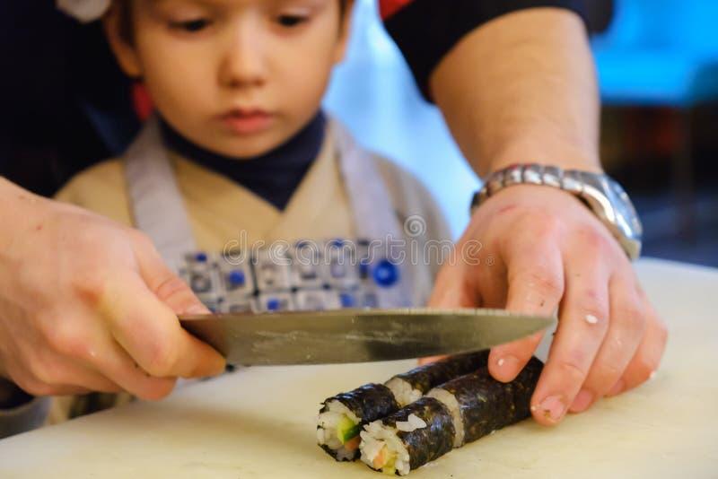 Sushirolle, die Vorbereitung, Nahaufnahme auf Chefhänden mit einem Messer macht stockbilder