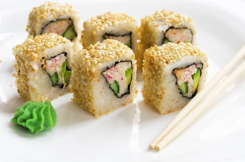 Sushirolle mit Ess-Stäbchen Japanisches Lebensmittel der Sushi im Restaurant Kalifornien-Sushirollensatz mit Avocado, Gemüse, Rog lizenzfreies stockbild