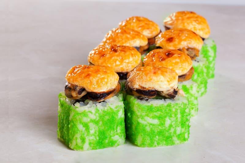 Sushirolle mit Miesmuscheln und grünem tobiko Kaviar bedeckt gebackenen Käse auf einer weißen Hintergrundnahaufnahme für das Menü lizenzfreies stockbild
