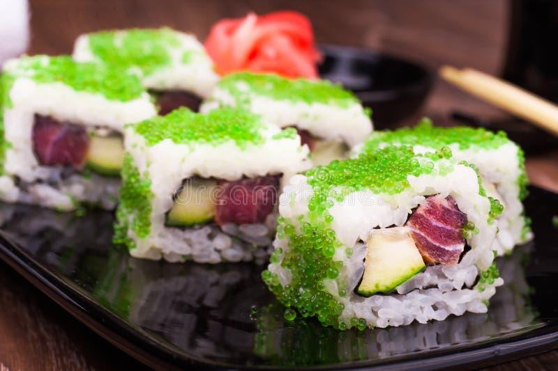 Sushirolle stellte in grünen Kaviar mit Ingwer, Sojasoße, Tuch und Essstäbchen ein stockfoto