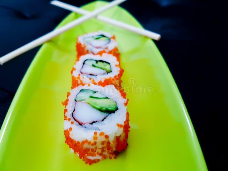 Sushirollen auf einer grünen Platte mit Essstäbchen - Avocado und Krabbe maki mit tobiko Kaviar auf dunklem Hintergrund lizenzfreies stockbild