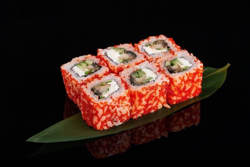 Sushirollen machten vom Reis, von geräuchertem Aal-, Frischkäse und vom Rogen des fliegenden Fisches - tobiko Kaviar stockfoto