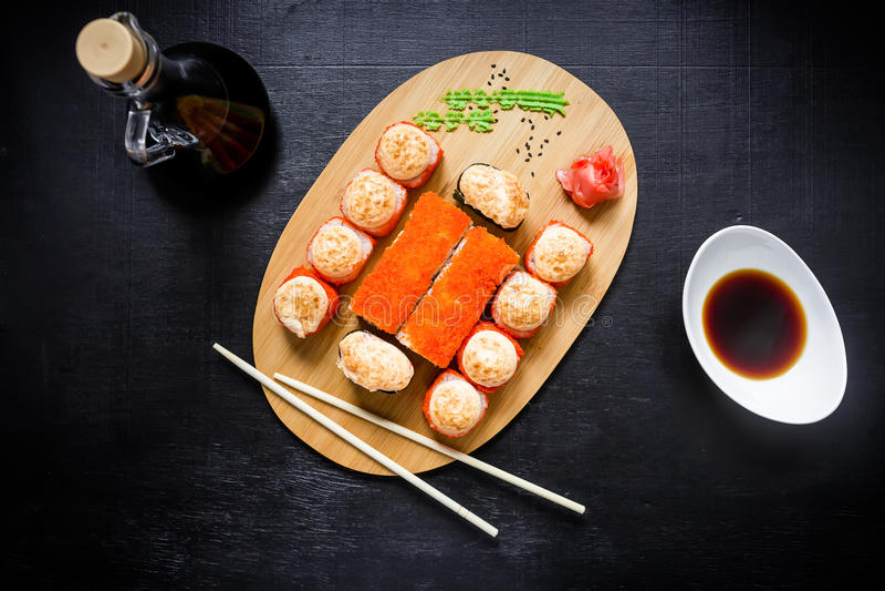 Sushirollen, Sojasoße und Essstäbchen auf einem schwarzen Hintergrund Japanische Naturkost Beschneidungspfad eingeschlossen Flach lizenzfreie stockfotografie