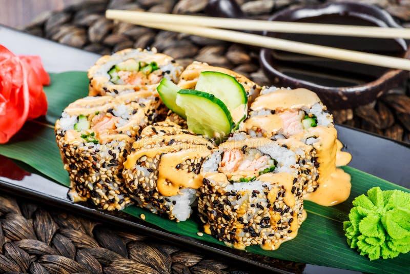 Sushirollen stellten mit Garnelentempura, -gurke, -zwiebel, -avocado und -indischem Sesam auf schwarzem Stein auf Bambusmatte, se stockfotografie