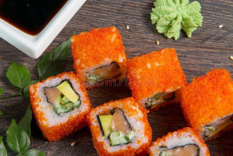 Sushirullar och kaviar på den svarta trätabellen Japansk mat fotografering för bildbyråer