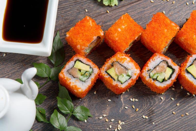 Sushirullar och kaviar på den svarta trätabellen Japansk mat arkivfoto