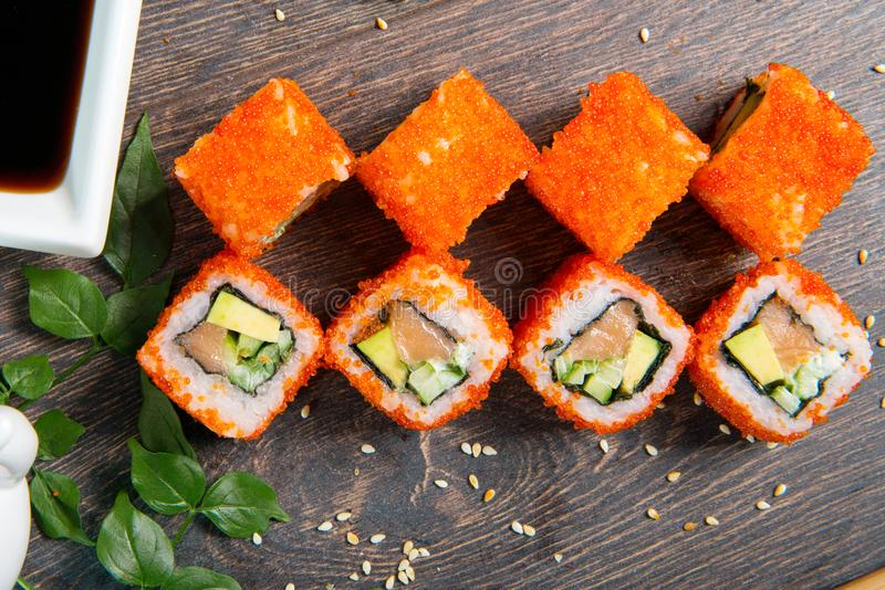 Sushirullar och kaviar på den svarta trätabellen Japansk mat royaltyfria bilder