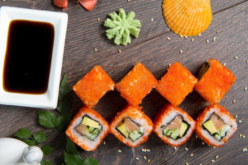 Sushirullar och kaviar på den svarta trätabellen Japansk mat arkivbild