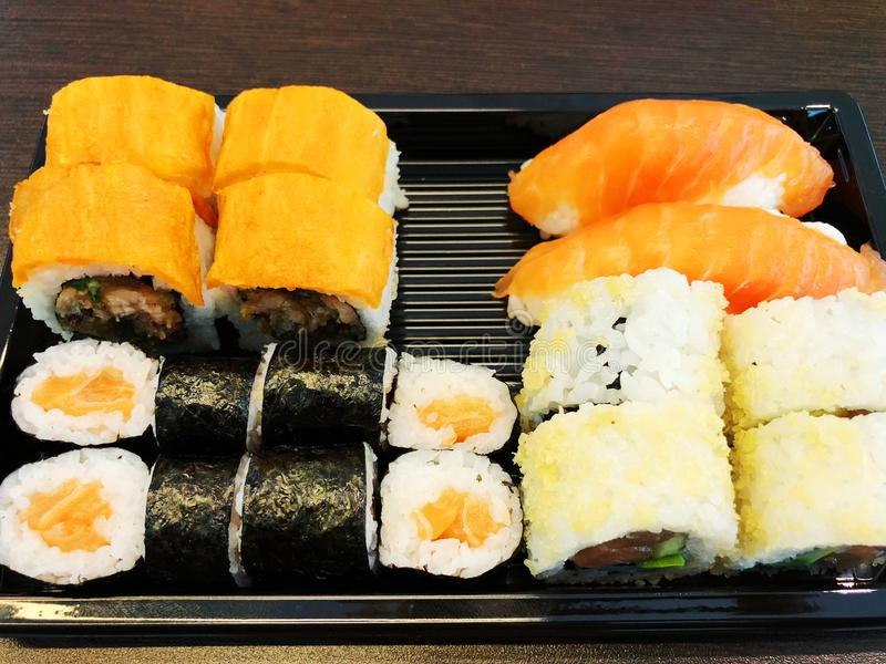 Sushirullar som rymmer vid pinnar En traditionell maträtt av japansk kokkonst royaltyfria bilder