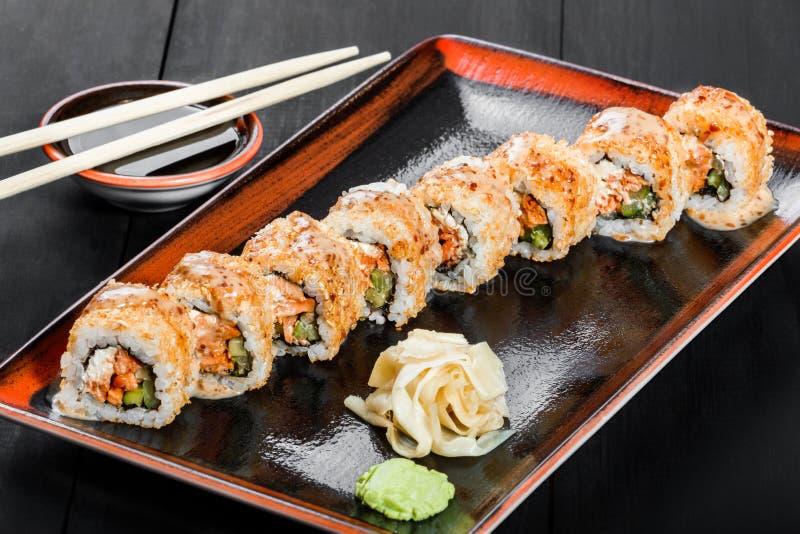 Sushirulle - Maki Sushi som göras av laxen, gurkan, avokadot och gräddost på mörk träbakgrund fotografering för bildbyråer