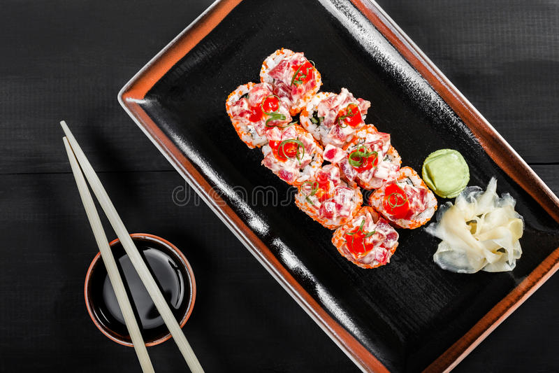 Sushirulle - Maki Sushi som göras av tonfisk, den röda kaviaren, gurkan, avokadot och gräddost på mörk träbakgrund royaltyfri bild