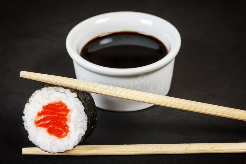 Sushirulle med pinnar och soya arkivfoto