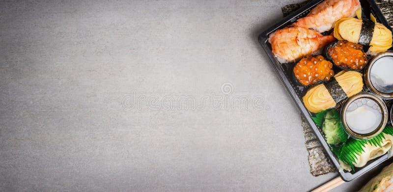 Sushisatz im Transportkasten auf grauem Steinhintergrund, Draufsicht, Platz für Text lizenzfreie stockbilder