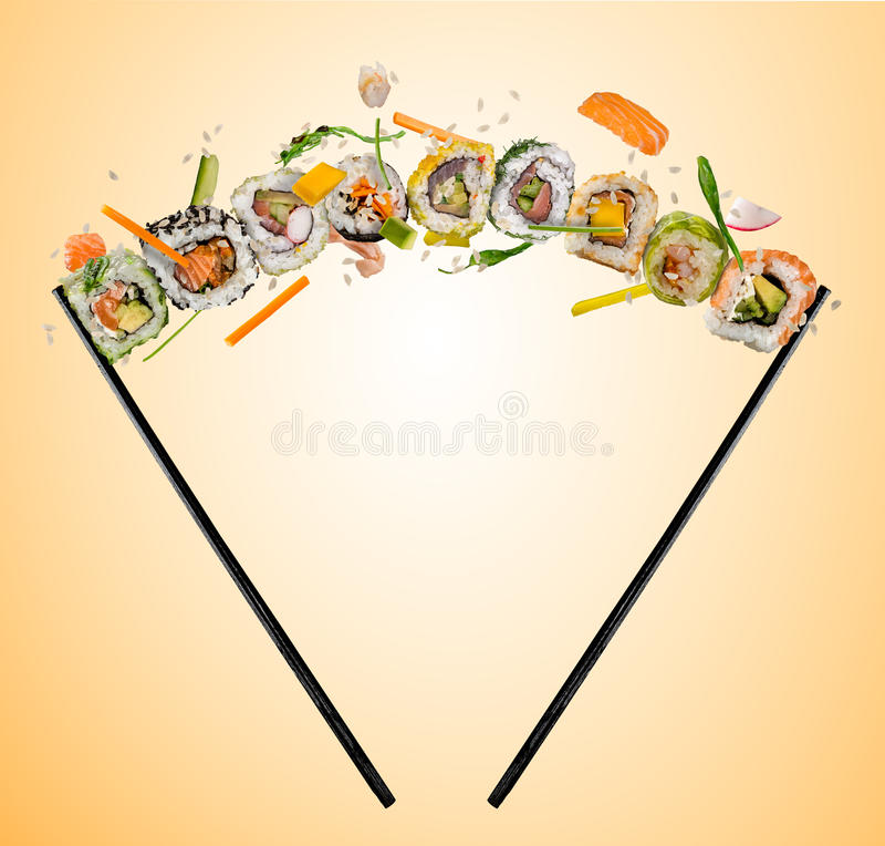 Sushistukken tussen eetstokjes, op gekleurde achtergrond worden geplaatst die royalty-vrije stock foto's