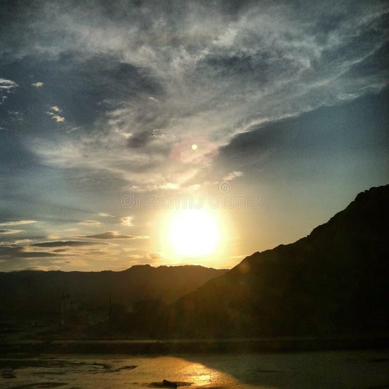 Susnet et nuages au-dessus des montagnes se reflétant de l'eau images stock
