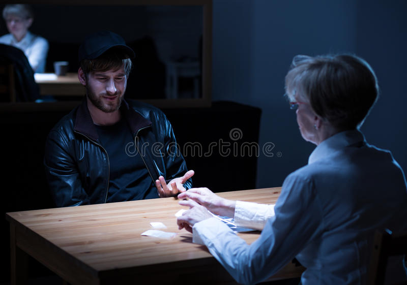 Suspect responding to policewoman questions. Photo of young suspect wearing cap responding to policewoman guestions stock image