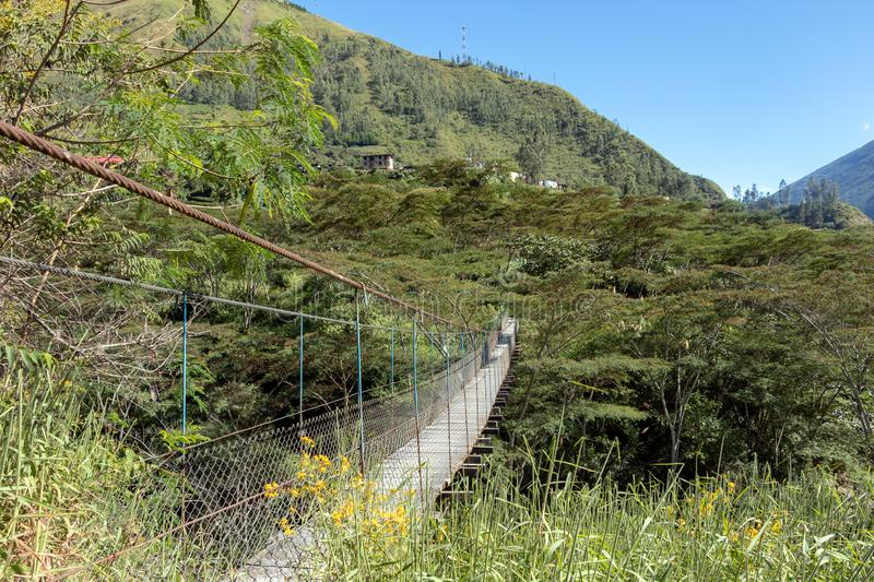 Suspended bridge hanging above the Santa Teresa River in green lush valley. Trek to Machu Picchu, Peru. Suspended bridge hanging above the Santa Teresa River in royalty free stock image