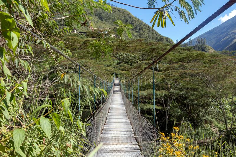 Suspended bridge hanging above the Santa Teresa River in green lush valley. Trek to Machu Picchu, Peru. Suspended bridge hanging above the Santa Teresa River in royalty free stock photography