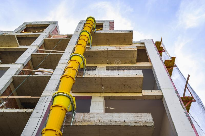 Suspended sections of yellow garbage chute on a facade of building under construction against blue sky with white cloud. Low angle view royalty free stock image