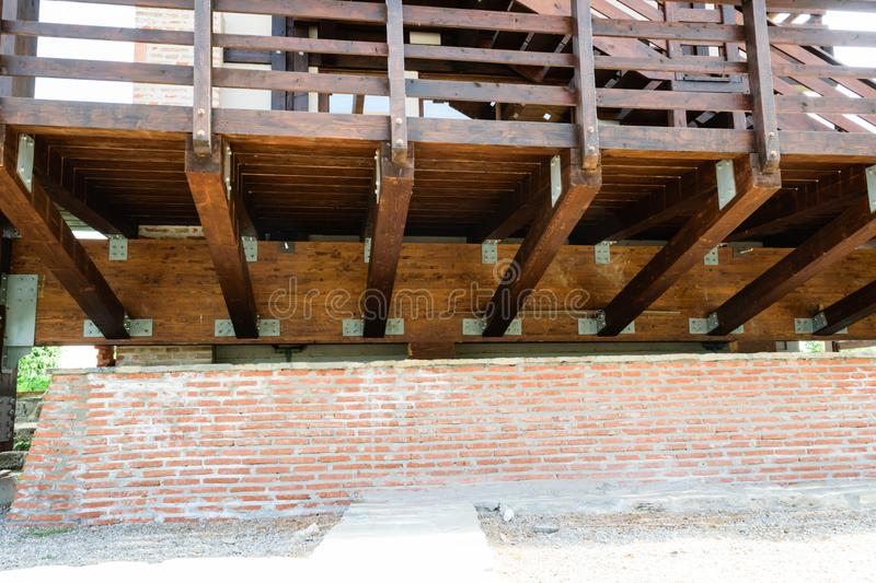 Suspended solid wood deck structure detail. Raised wooden deck and hand guard with brick wall foundation. royalty free stock photo