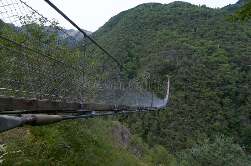 Suspended Tibetan bridge. View of the 270m long Tibetan bridge `Carasc` that allows the passage of the rugged valley that separates the communities of Sementina stock photography