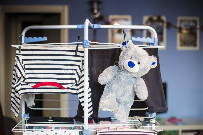 Suspensão cinzenta do urso de peluche seca na cremalheira com roupa fotos de stock