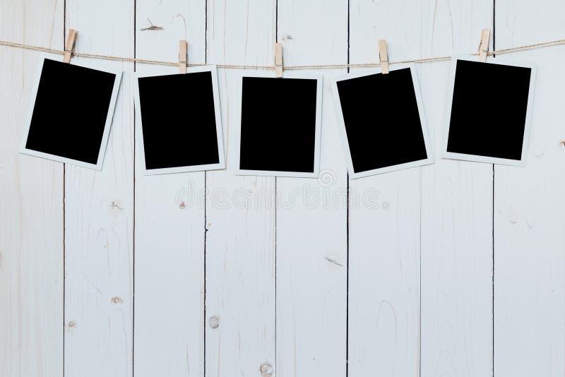 Suspensão vazia do quadro de cinco fotos no fundo da placa de madeira foto de stock