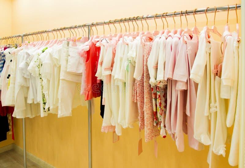 Suspensión con la ropa de los niños, fondo para la tienda de los niños imágenes de archivo libres de regalías