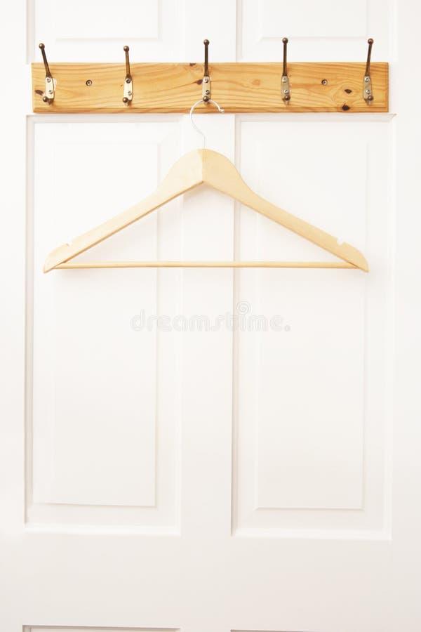 Suspensión vacía de madera para la ropa aislada en la puerta blanca Moda, concepto de la belleza Aislado imágenes de archivo libres de regalías