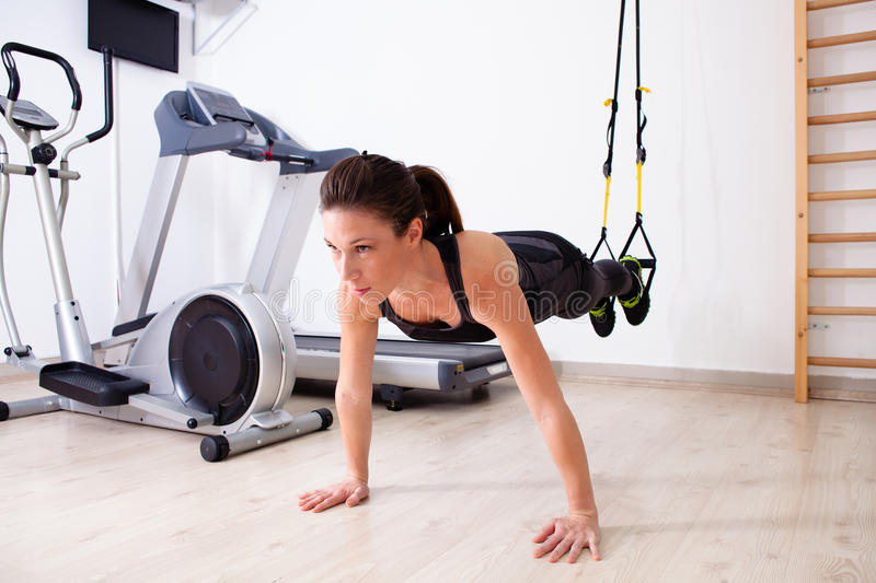 Suspension arm training. Girl doing pilates in studio royalty free stock photography