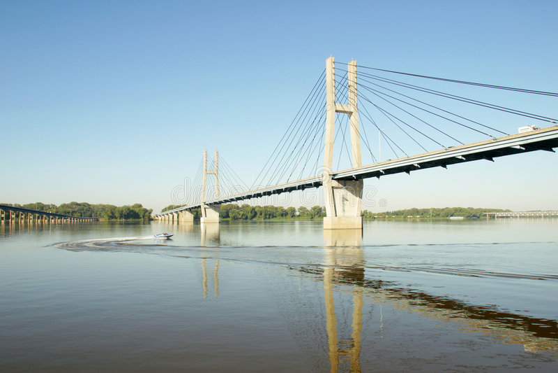 Suspension Bridge. A small motor boat circling under a suspension bridge stock images