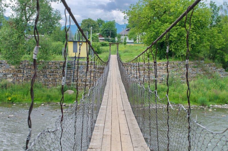 Suspension bridge across the mountain river royalty free stock photos