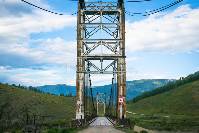 Suspension bridge across mountain river. Evening light, blue sky royalty free stock image