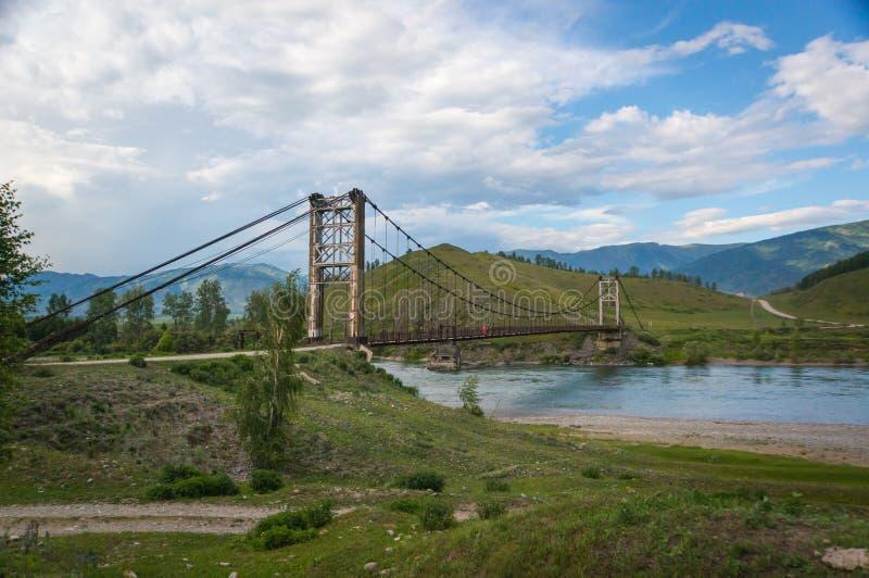 Suspension bridge across mountain river. Evening light, blue sky royalty free stock photo