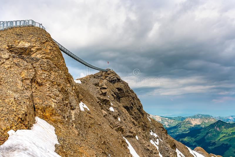 Suspension bridge connecting two mountain peaks at an altitude of 3000 meters. Summer scene at Les Diablerets Glacier stock photo