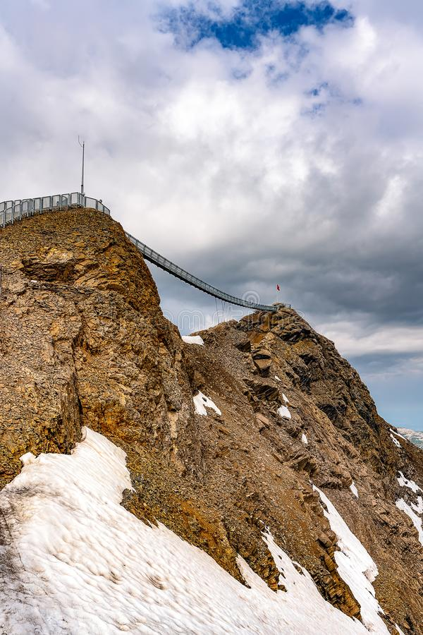 Suspension bridge connecting two mountain peaks at an altitude of 3000 meters. Summer scene at Les Diablerets Glacier royalty free stock photos