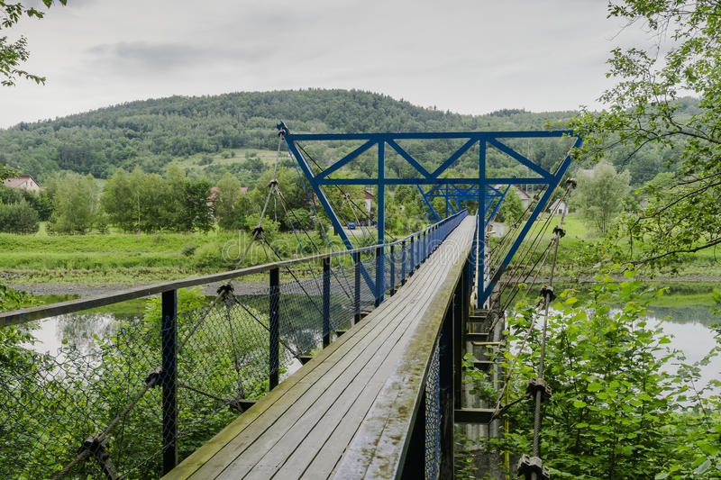 Suspension bridge. Creative Commons presents hanging over the river footbridge for pedestrians in Small village Rożnów , Poland . Europe royalty free stock image