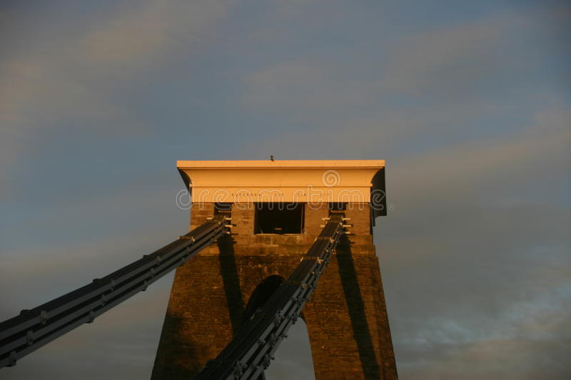 Clifton suspension bridge. Top of a supporting pier of the Clifton suspension bridge in Bristol. Glowing in the evening sunlight. Background is sky with sunlit stock images