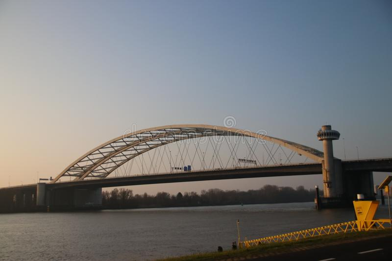 The suspension bridge named van Brienenoordbrug and offices in the morning sun in Rotterdam stock photo