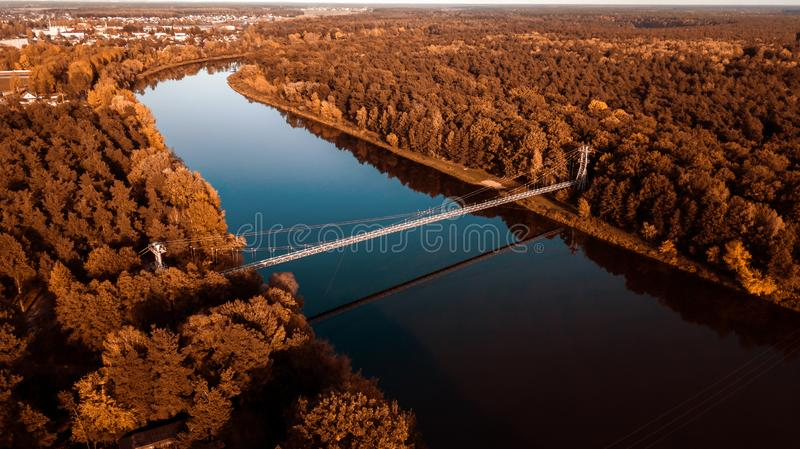 Suspension bridge over the river. aerial photography from a drone. Autumn panorama stock photos
