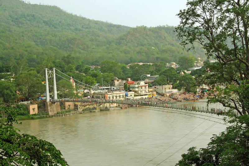 Suspension bridge on river ganga, rishikesh. Lukshman jhoola suspension bridge on the river ganga/ ganges in the hindu holy city of Rishikesh India famous for stock photography