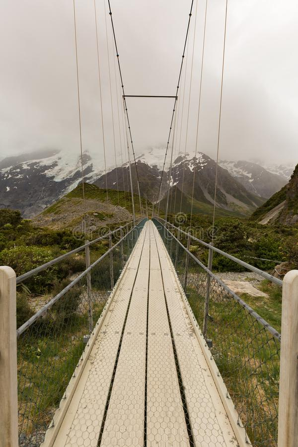 Suspension bridge and wooden path in to national park New Zealand royalty free stock photo