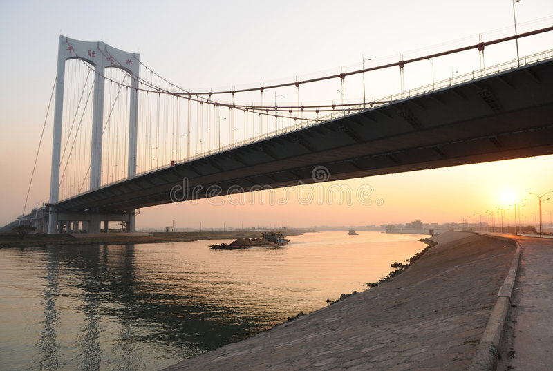 Suspension brige over river. A steel and concrete suspension bridge over a river in sunset, Foshan,Guangdong,China stock image