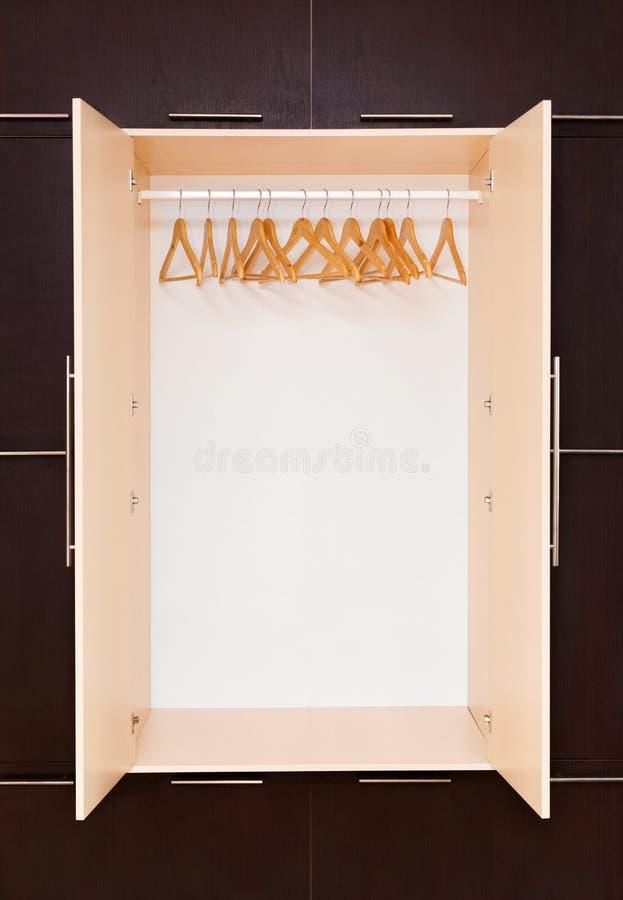 Suspensiones de capa de madera en el carril de la ropa en el armario imagen de archivo libre de regalías